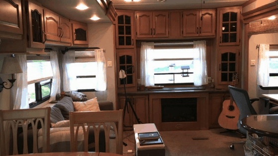 For a simple way to brighten up an RV living room during your remodel, consider white curtains. These were made with inexpensive bed sheets. One of the best ways of rejuvenating your dark RV interior is by updating your RV window treatments. Check out these simple, affordable RV window treatment ideas.