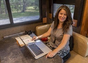 A smiling Camille Attell of More Than A Wheelin', working on her laptop in her RV's booth dining table..