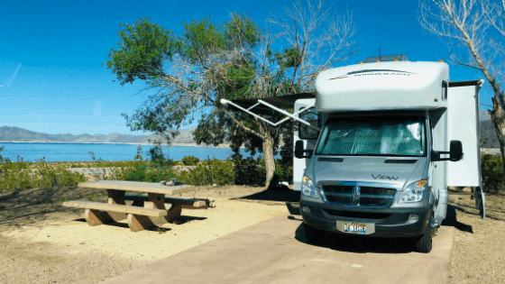 A photo of a Winnebago View parked on a paved RV site pad with its awning and slides out. The site is mostly dirt with a picnic table and shrubs and deciduous trees around it. The bright blues of Lake Mead and the sky are in the background with some mountains off in the distance.